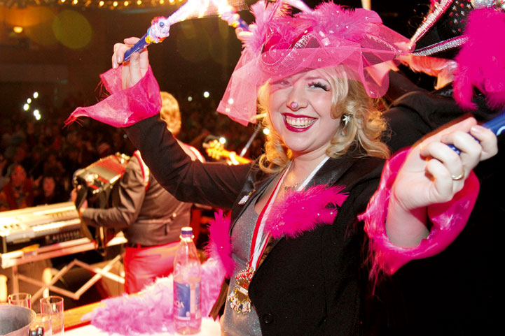 Frau mit pinkem Kostuem feiert Karneval